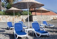 Chaises longues et parapluies vides avec un toit couvert de chaume sur la plage Photographie stock libre de droits