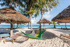 Chaises longues faites main, parapluies de paille et hamac sur une plage Photographie stock libre de droits