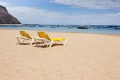 Chaises longues jaunes sur la plage de mer Photo stock