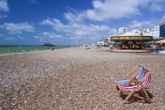 Chaises longues rayées sur la plage R-U de Brighton Photo stock