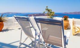 Chaises longues sur la belle terrasse fleurie blanche avec la vue de mer dans Santorini, Grèce Photos stock