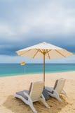 Chaises longues sur une belle plage tropicale arénacée Photos libres de droits