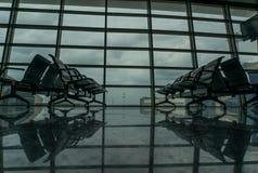 Chaises pour des passagers dans le hall d'aéroport Photos libres de droits