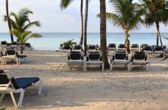 Chaises sur la plage sur le coucher du soleil Photographie stock
