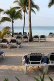 Chaises sur la plage sur le coucher du soleil Photo stock