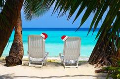 Chaises sur le chapeau rouge tropical de plage et de Noël de Santa Claus Photos stock