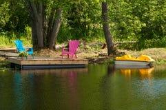 Chaises vertes et roses sur un dock Image libre de droits