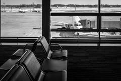 Chaises vides dans le hall de départ à l'aéroport, avec la porte et un avion Concepts de voyage et de transport noir Photos stock