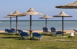 Chaisevardagsrum och paraply på stranden mot den blåa himlen och Royaltyfria Foton