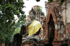 Chaiwattanaram temple in Ayutthaya and Buddha. Ancient ruins of Chaiwattanaram temple in and sculpture of Buddha with yellow cloth in Ayutthaya in Thailand Stock Photos