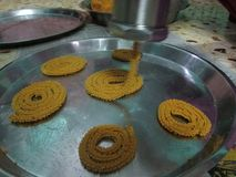 Chakli Snack. Close up click of Crispy and tasty group of chakli snack under the process of making from an equipment Royalty Free Stock Photo