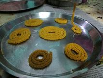 Chakli Snack. Close up click of Crispy and tasty group of chakli snack under the process of making from an equipment Stock Photos