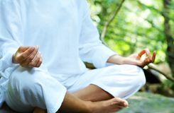 Chakra. Fragment like image of young woman practicing yoga in tropic environment Stock Image