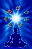 Chakra circle. Male silhouette figure in yoga position with the chakras symbols over blue background with white flare Stock Photo