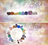 Chakra Crystal Headers x 2. Two different headers with chakra colored tumbled semi precious gemstones on a bokeh sparkling ethereal pastel colored background royalty free stock image