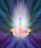 Chakra Healer. Healer's hands emerging from feather like multicolored energy formation background, cupped with seven chakra vortexes hovering above in a misty royalty free stock image