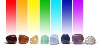 Chakra Healing Crystals Color Chart. Row of chakra colored tumbled gem stones in a row on a white background with the corresponding chakra color above each stone Stock Photos
