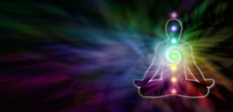 Chakra Meditation Website Header. Wide dark banner with a rainbow colored spiral formation in the background and a male silhouette seated in lotus position on Stock Image