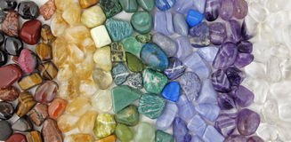 Chakra tumbled healing stones crsytal healing background. Wide selection of different chakra coloured tumbled healing stones lined up vertically left to right stock image