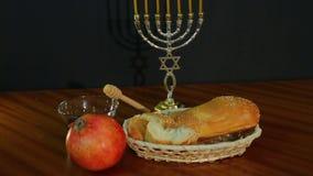 Chalá, mel e romã para o feriado de Rosh Hashanah ao lado do menorah com velas video estoque