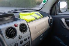 Chaleco amarillo en un coche del tablero de instrumentos en protesta contra aumentos del impuesto imagenes de archivo