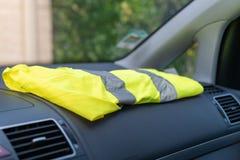 Chaleco amarillo en un coche del tablero de instrumentos en protesta contra aumentos del impuesto imagen de archivo libre de regalías