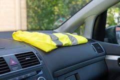 Chaleco amarillo en un coche del tablero de instrumentos en protesta contra aumentos del impuesto fotos de archivo