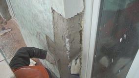 Chaleco del trabajador de la construcción y pared wiearing de los yesos del casco con el cuchillo del spackle almacen de video