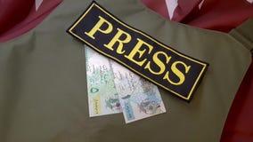 Chaleco a prueba de balas y dinero en la bandera nacional metrajes