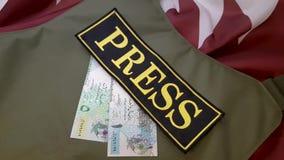 Chaleco a prueba de balas y dinero en la bandera nacional almacen de metraje de vídeo