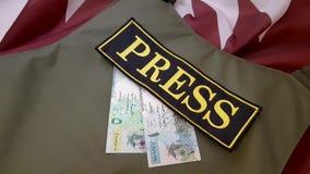 Chaleco a prueba de balas y dinero en la bandera nacional almacen de video