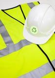 Chaleco y casco de la seguridad con el reciclaje de símbolo sobre el fondo blanco Imagenes de archivo