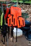 Chalecos salvavidas anaranjados y amarillos en la suspensión Fotos de archivo libres de regalías