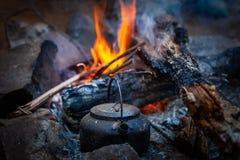 Chaleira da fogueira colocada perto dos carvões de queimadura fotos de stock