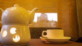 A chaleira da porcelana aqueceu-se sobre a vela de queimadura e o chá quente no copo de chá na tabela vídeos de arquivo