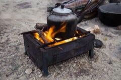 Chaleira de acampamento fumado no fogo em um acampamento exterior na sobremesa Fotografia de Stock