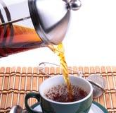 Chaleira de chá fresca de derramamento no copo verde foto de stock