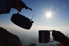 Chaleira e copo da silhueta no nascer do sol com fundo da montanha fotografia de stock royalty free