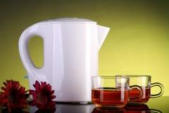 Chaleira elétrica e dois copos de chá com flores imagem de stock royalty free