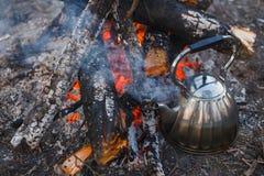 A chaleira est? pelo fogo no lago fotos de stock