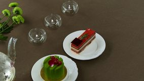 Chaleira transparente bonita do bule com chá preto verde saboroso com maçã, com velas e com a sobremesa no foto de stock