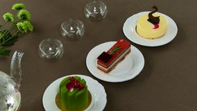 Chaleira transparente bonita do bule com chá preto verde saboroso com maçã, com velas e com a sobremesa no fotografia de stock