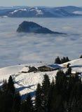 Chalet über Wolken im Winter Stockbild