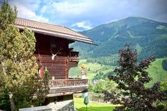 Chalet con i picchi e la valle alpini verdi Fotografie Stock Libere da Diritti