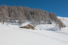 Chalet covered by snow in italian alps. Chalet made of stones covered by snow in a hill italian alps Royalty Free Stock Image