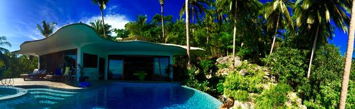 Chalet de la piscina entre las palmeras foto de archivo libre de regalías