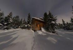 Chalet della casa di panorama durante precipitazioni nevose nella foresta di inverno degli alberi alla notte nella luce della lun immagini stock
