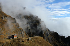 Chalet in the foggy mountains Stock Images