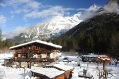 Chalet in French Alps in Chamonix with a panorama of mountains covered in snow in winter. Chalet and a hut in French Alps in Chamonix with a panorama of Royalty Free Stock Image