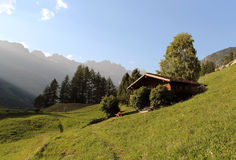 Chalet on the grass. Family's traditional chalet in the middle of a grass field between Valtournenche's Alps (ITALY Stock Photo